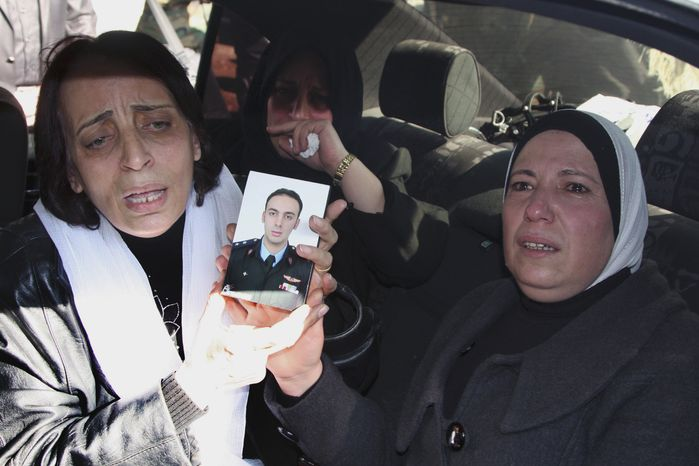 In this photo taken during a government-organized tour for the media, relatives of William Al-Saleh, one of six elite pilots who the military said were killed in an ambush on Thursday, hold his portrait as they mourn during his funeral procession in Syria's Homs province on Saturday, Nov. 26, 2011. (AP Photo/Bassem Tellawi)