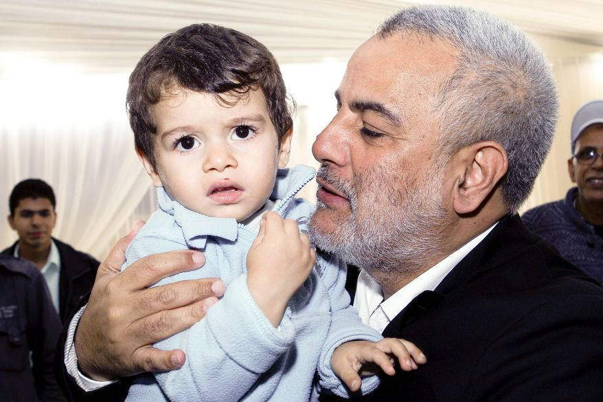 Abdelilah Benkirane, the secretary general of Morocco's Islamist Justice and Development Party, holds his small son, Hamza, at the party's headquarters in Rabat, Morocco, on Sunday, Nov. 27, 2011, after it became clear that his party was on track to become the largest in Morocco's new parliament. (AP Photo/Abdeljalil Bounhar)