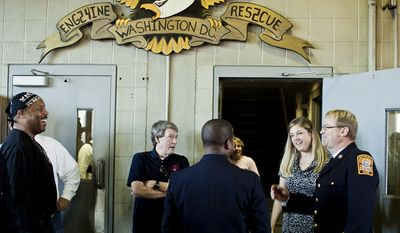 Lou Reid, from left, who served with Engine Co. 24 for 11 years, and Doug Wheeler, a 34-year veteran of the D.C. Fire Department and former Captain of Engine Co. 24, talk with Capt. Chris Sefton, at right, and his wife Stacy during Engine Company 24's centennial celebration.(T.J. Kirkpatrick/ The Washington Times)