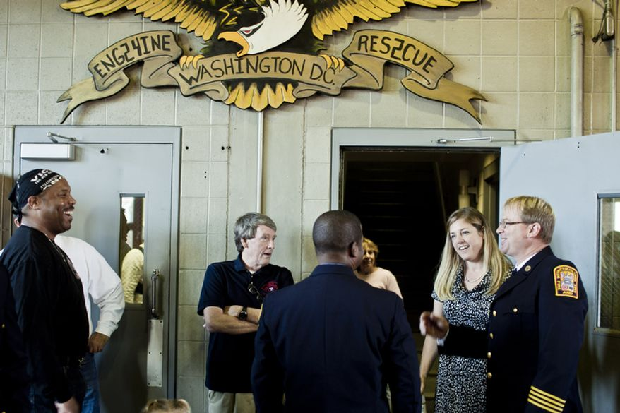 Lou Reid, from left, who served with Engine Co. 24 for 11 years, and Doug Wheeler, a 34-year veteran of the D.C. Fire Department and former Captain of Engine Co. 24, talk with Capt. Chris Sefton, at right, and his wife Stacy during Engine Company 24's centennial celebration.