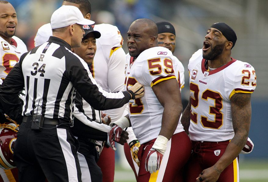 Referee Clete Blakeman, left, holds back Washington Redskins' London Fletcher (59) and DeAngelo Hall (23) after a shoving match during the coin toss in the first quarter of an NFL football game against the Seattle Seahawks. (AP Photo/Ted S. Warren)