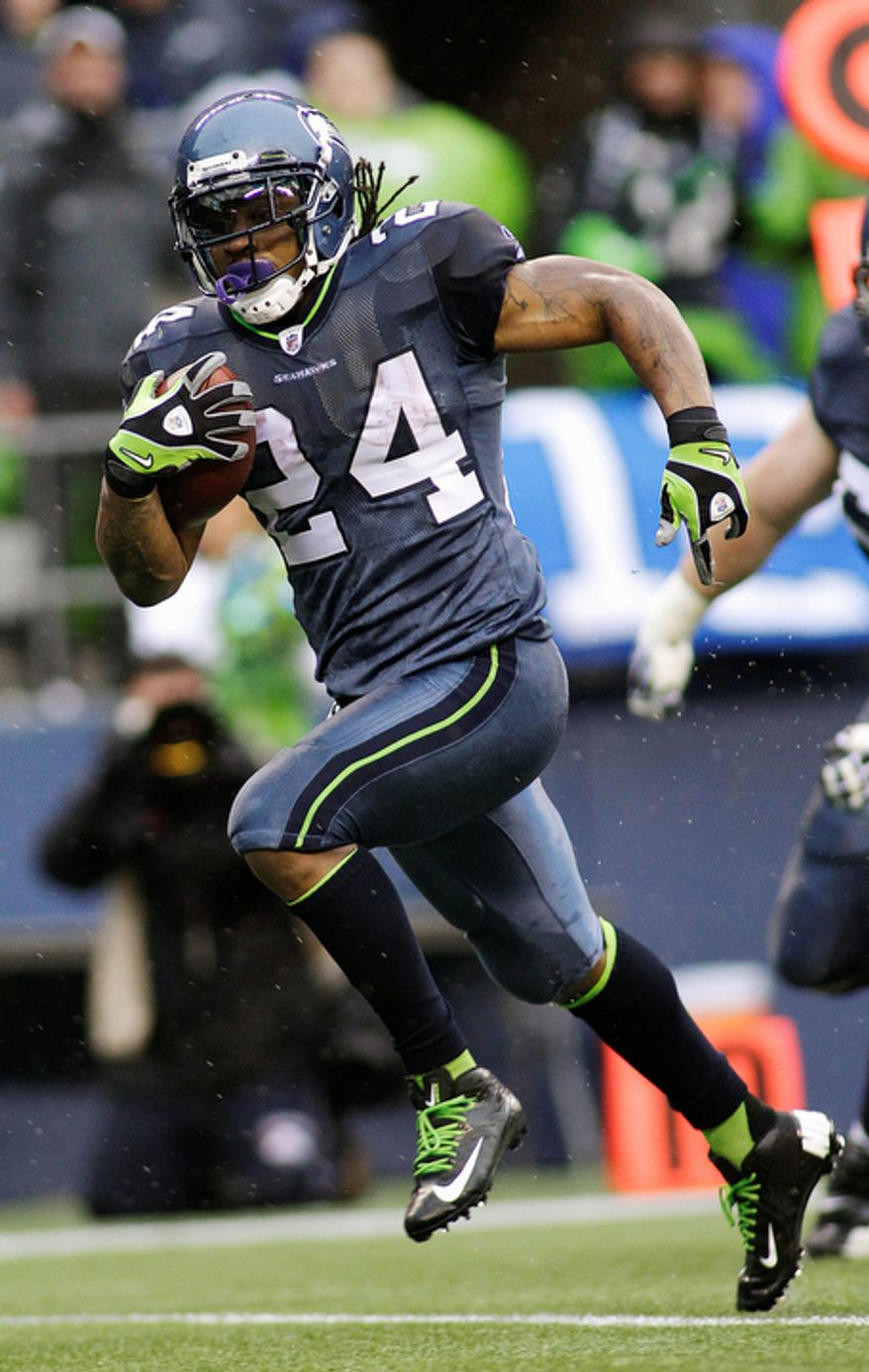 Seattle Seahawks' Marshawn Lynch runs the ball in for a touchdown against the Washington Redskins in the first half of an NFL football game. (AP Photo/Ted S. Warren)