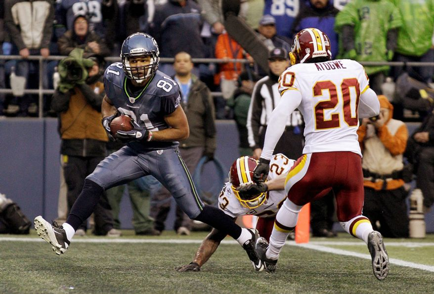 Seattle Seahawks wide receiver Golden Tate makes a touchdown reception under pressure from Washington Redskins' DeAngelo Hall (23) and Oshiomogho Atogwe (20) in the second half. (AP Photo/Ted S. Warren)