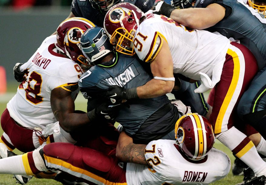Seattle Seahawks quarterback Tarvaris Jackson is sacked for a 9-yard loss by Washington Redskins' Stephen Bowen (72) and Brian Orakpo, left, as Ryan Kerrigan (91) comes in late in the second half. The Redskins won 23-17. (AP Photo/Elaine Thompson)