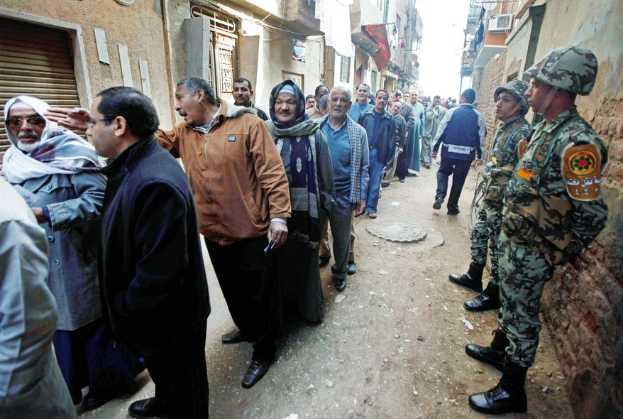 Egyptian army soldiers stand guard as voters line up outside a polling center in Assuit, 200 miles south of Cairo, on Monday. Voting began on Monday in Egypt's first parliamentary elections since longtime authoritarian leader Hosni Mubarak was ousted in a popular uprising nine months ago. The vote is a milestone many Egyptians hope will usher in a democratic age. (Associated Press)