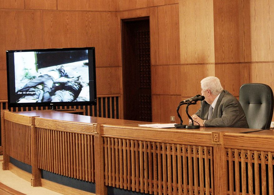 Foreign Minister Walid al-Moallem watches videos of corpses during a news conference Monday to bolster the Syrian regime's contention that armed gangs are behind the country's violence. A U.N. probe condemns the regime for violence against protesters.