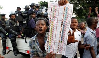 Supporters of opposition candidate Etienne Tshisekedi display what they claim are bogus election ballots they say were found in the Bandal commune of Kinshasa, Democratic Republic of Congo, on Monday. (Associated Press)