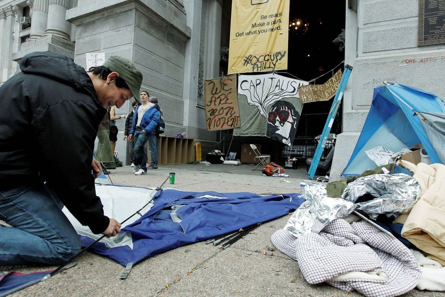 Adam Hill takes down his tent at the Occupy Philadelphia encampment at City Hall on Monday. Dozens of Occupy Philadelphia protesters planned to try to hold down their encampment outside City Hall on Monday, a day after a city-imposed deadline. (Associated Press)
