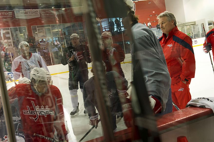 New Washington Capitals Head Coach Dale Hunter (right) watches instructions being given during a time out in the practice, as he takes to the ice with his team as they practice together for the first time, at the Kettler Capitals Iceplex in Arlington, Va, Monday, November 28, 2011. (Rod Lamkey Jr/ The Washington Times)