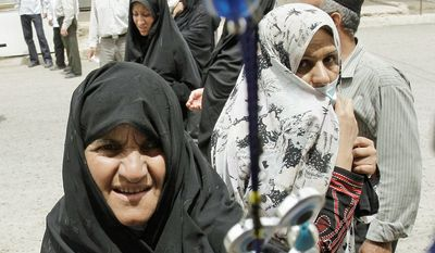 Iranian pilgrims buy Shiite amulets near the al-Askari shrine in Samarra, 60 miles north of Baghdad. Many in Iraq's Shiite majority are wary of infringement of their country's sovereignty and afraid of being overrun by the Iranian theocracy. (Associated Press)