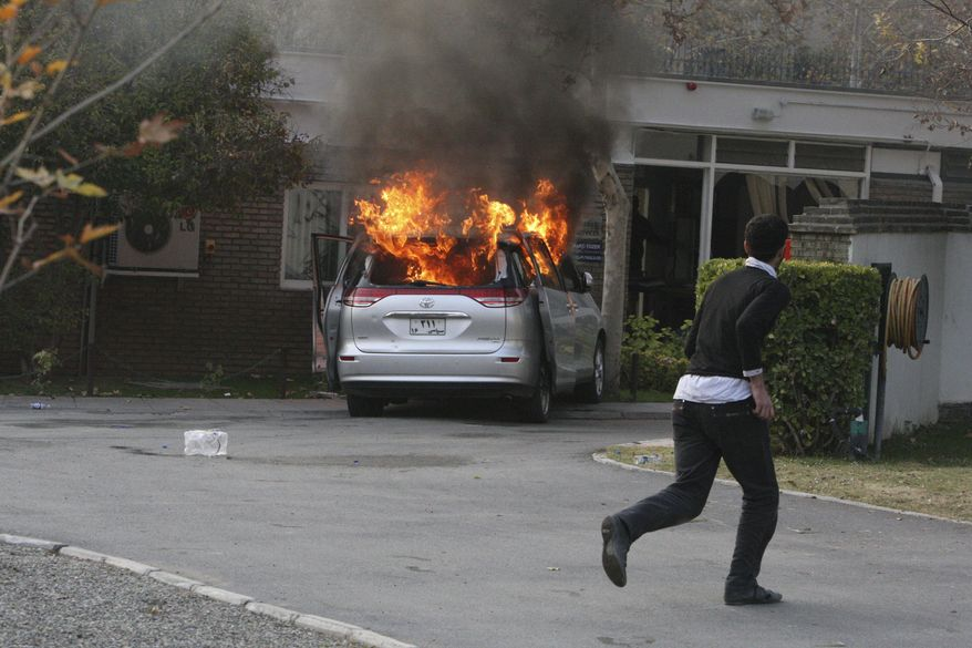A hard-line Iranian protester runs inside the British Embassy in Tehran as a diplomatic vehicle is set on fire by demonstrators who stormed the embassy compound on Tuesday, Nov. 29, 2011. (AP Photo/Vahid Salemi)