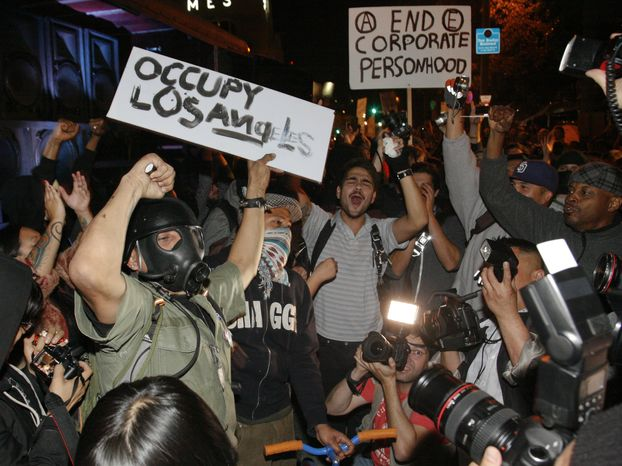 Wall Street protesters dance to music as they remain at the camp in front of Los Angeles City Hall in Los Angeles on Sunday, Nov. 27, 2011. Los Angeles Mayor Antonio Villaraigosa stated Friday that the protesters' campsite will be dismantled, beginning at 12:01 a.m. Monday. (AP Photo/Jason Redmond)