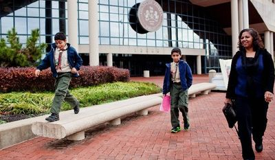 Brinda Grapin and her sons Sean, 9, (left) and Eric, 11, leave the Fairfax County Board of Zoning Appeals meeting on Wednesday after being granted permission to keep a treehouse they built in their front yard in Falls Church. An initial hearing in September rebuffed the family's attempt to keep the structure, but they won a variance on appeal. (T.J. Kirkpatrick/The Washington Times)