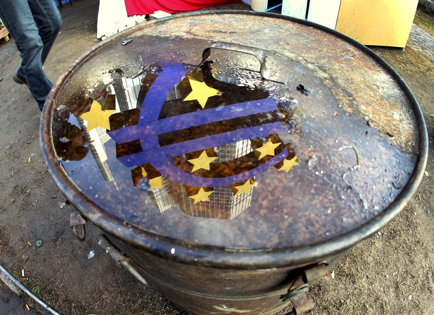The Euro sculpture is reflected in a puddle on the lid of a bin that stands in the Frankfurt Occupy camp at the European Central Bank in Frankfurt, Germany, Wednesday, Nov.30, 2011. (AP Photo/Michael Probst)
