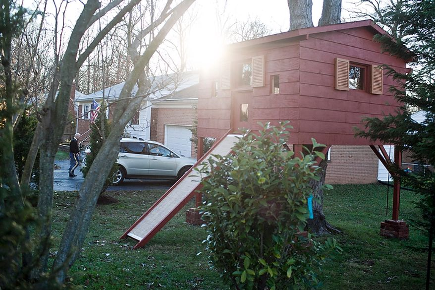 A treehouse sits in the front yard of the Grapin family home in Falls Church, Va., on Nov. 30, 2011. Mark Grapin, walking in background, an Army National Guard chief warrant officer, testified before the Fairfax County Board of Zoning and Appeals Wednesday in support of an ordinance that would allow him to keep a treehouse in his front yard. An initial hearing in September rebuffed Grapin's attempt to keep his treehouse in place for his two sons, but an appeal was allowed and Wednesday's hearing granted an ordinance that gives the family five years until the treehouse must be removed. (T.J. Kirkpatrick/The Washington Times)