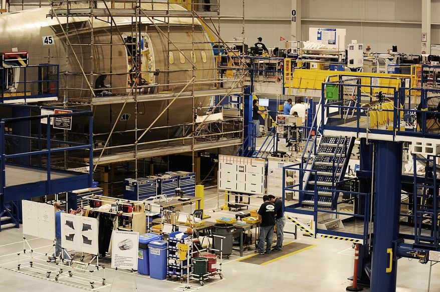 Boeing employees work in the 787 Dreamliner aft-body assembly building in June in Charleston, S.C. It's not immediately clear how a National Labor Relations Board dispute involving the South Carolina plant will be affected by aerospace giant Boeing reaching a tentative labor contract with the Machinists union this week. (Jeremy Lock/Special to The Washington Times)