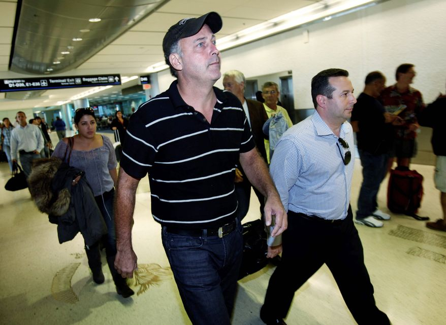 Gary Giordano, center, a Maryland businessman who had been jailed in Aruba on suspicion of involvement in the presumed death of his traveling companion, walks through Miami International Airport in Miami with attorney Jose Baez, right, after leaving Aruba, Wednesday, Nov. 30, 2011. Giordano denies any wrongdoing in the disappearance of Robyn Gardner. A judge ordered his release after ruling prosecutors didn't have enough evidence to justify holding him longer. (AP Photo/Wilfredo Lee)
