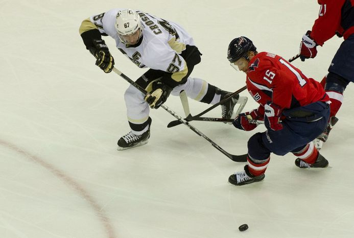 Pittsburgh Penguins' Sidney Crosby battles for the puck with Washington Capitals' Jeff Halpern in the second period at the Verizon Center in Washington, Thursday, Dec. 1, 2011. The Caps lost 2-1 and have struggled to create offense lately in part to their difficulty moving the puck out of the defensive zone. (Rod Lamkey Jr/ The Washington Times)