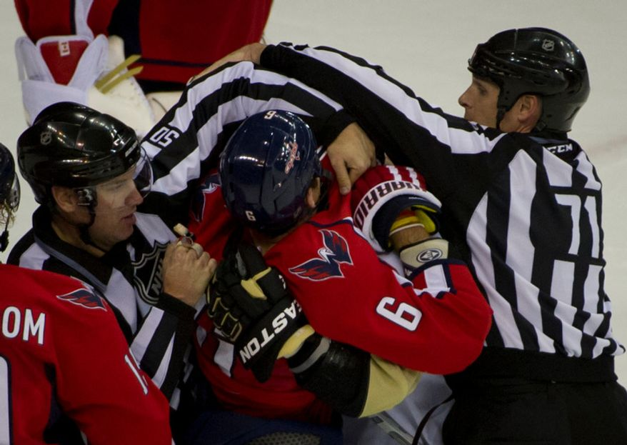 Referees break up a fight between Capitals Dennis Wideman (6) and Penguins Jordan Neal (18) in the second period as the Washington Capitals host the Pittsburg Penguins at the Verizon Center in Washington, DC, Thursday, December 1, 2011. (Rod Lamkey Jr/ The Washington Times)