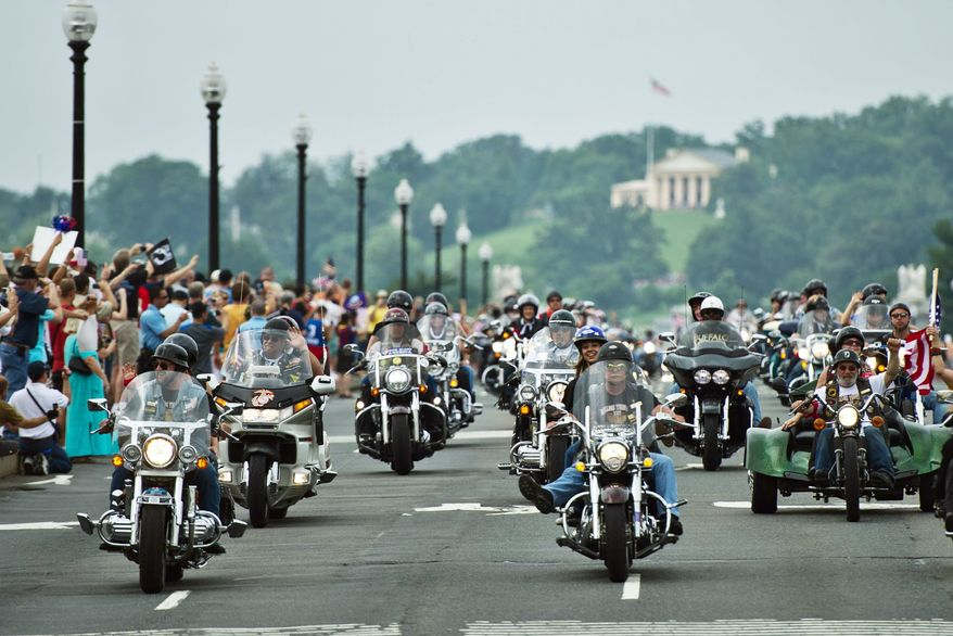 ** FILE ** Bikers in the Rolling Thunder motorcycle rally ride across Memorial Bridge in Washington, D.C. In Michigan, the repeal of the helmet law is gaining traction. (Drew Angerer/The Washington Times)