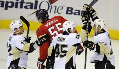 Pittsburgh Penguins right wing Craig Adams celebrates his goal with Arron Asham (45) and Richard Park (12) as Washington Capitals defenseman Jeff Schultz skates away during the first period Thursday, Dec. 1, 2011, in Washington. (AP Photo/Nick Wass)