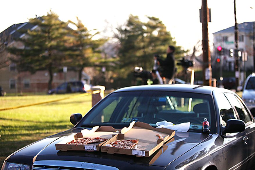 A pizza sits on the hood of a press vehicle as media watched all day as FBI and IRS Criminal Investigative Division agents serve a search warrant on the home of Washington D.C. City Council member Harry Thomas, Jr., on 17th Street NE in Washington, D.C., on Friday, December 2, 2011. (Pratik Shah./The Washington Times)