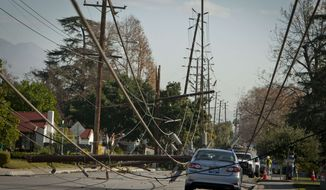 Crews from Southern California Edison power company work to clean up and restore power on Live Oak Avenue, Friday, Dec. 2, 2011, in Temple City, Calif. (AP Photo/Bret Hartman)