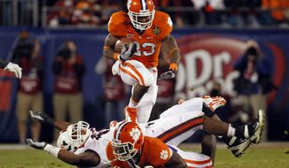 Clemson's Andre Ellington runs over a Virginia Tech player during the first half of the Atlantic Coast Conference championship NCAA college football game in Charlotte, N.C., Saturday, Dec. 3, 2011. (AP Photo/Bob Leverone)