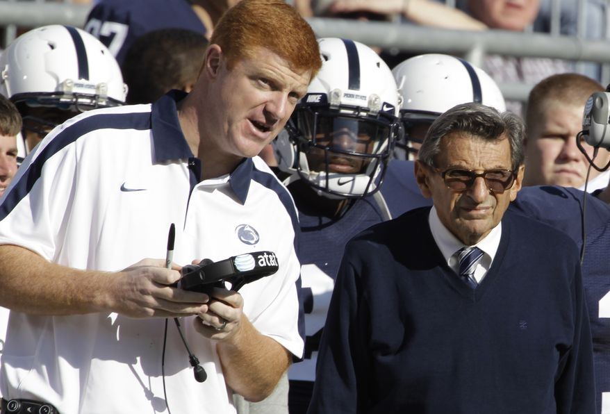 FILE - In this Oct. 8, 2011 file photo, Penn St. assistant football coach Mike McQueary, left, talks with head coach Joe Paterno during an NCAA college football game against Iowa, in State College, Pa. Penn State Athletic Director Tim Curley and Gary Schultz, the school's senior vice president for business and finance, face arraignment Monday, Nov. 7, 2011, on charges they lied to a grand jury investigating former defense coordinator Jerry Sandusky and failed to properly report suspected child abuse, a case that has left fans reeling. In 2002, State Attorney General Linda Kelly said, a graduate assistant, identified by two people familiar with the investigation as McQueary, saw Sandusky sexually assault a naked boy, estimated to be about 10 years old, in a team locker room shower. (AP Photo/Gene Puskar, File)