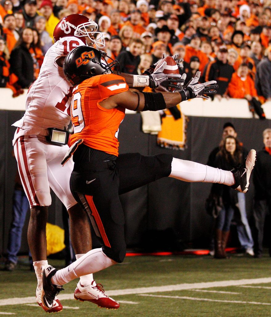 Oklahoma State cornerback Brodrick Brown intercepts a pass in the end zone intended for Oklahoma wide receiver Jaz Reynolds during Saturday's game. Oklahoma State staked its claim to being No. 2 with a 44-10 rout of the rival Sooners. (Associated Press)