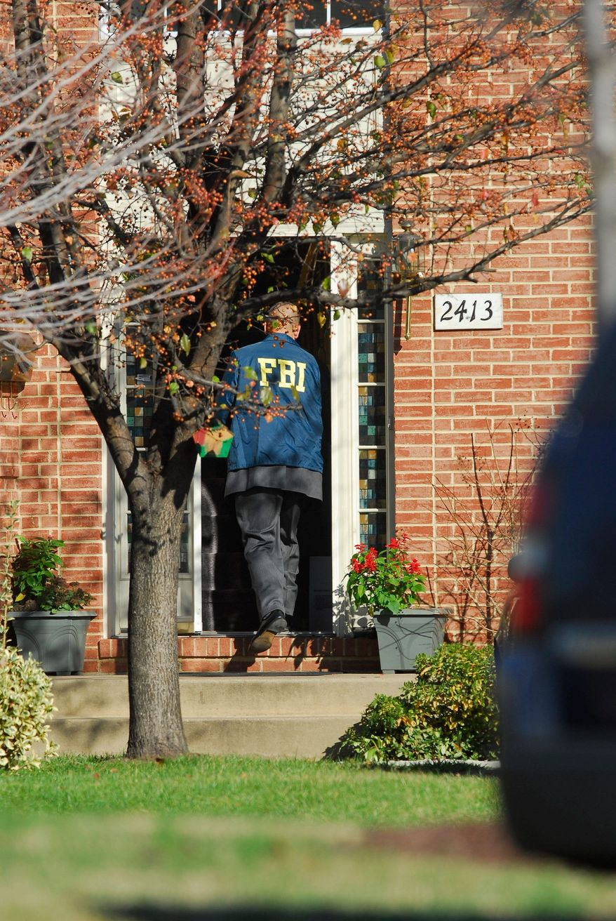 Agents from the FBI and the IRS' Criminal Investigative Division serve a search warrant at the home D.C. Council member Harry Thomas, Jr., on Friday. The agents were at Mr. Thomas' home for more than nine hours and seized a red motorcycle and Chevrolet Tahoe, among other items. (Pratik Shah/The Washington Times)