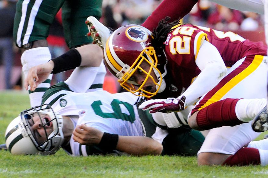New York Jets quarterback Mark Sanchez (6) reacts after being hit by Washington Redskins defensive back Kevin Barnes (22), which roughing the passer was called during third quarter action. (Preston Keres/For The Washington Times)