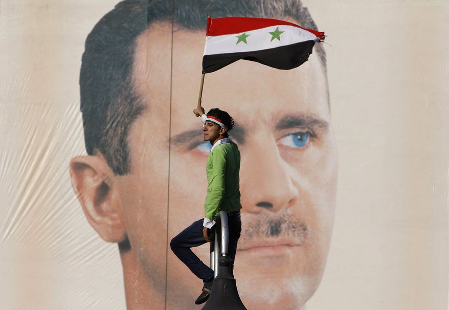 A pro-Syrian-regime demonstrator waves a Syrian flag as he stands in front of portrait of Syrian President Bashar Assad during a protest against sanctions in Damascus, Syria, on Friday, Dec. 2, 2011. (AP Photo/Muzaffar Salman)