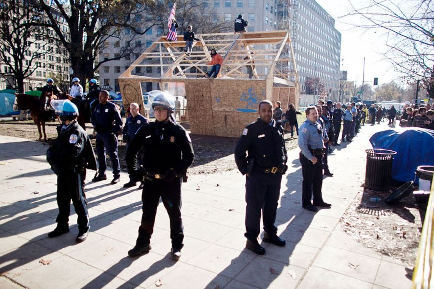 Park Police and MPD  form a perimeter around a new structure the was erected in McPherson Square, in Washington, D.C. on Dec. 4, 2011.(T.J. Kirkpatrick/ The Washington Times)