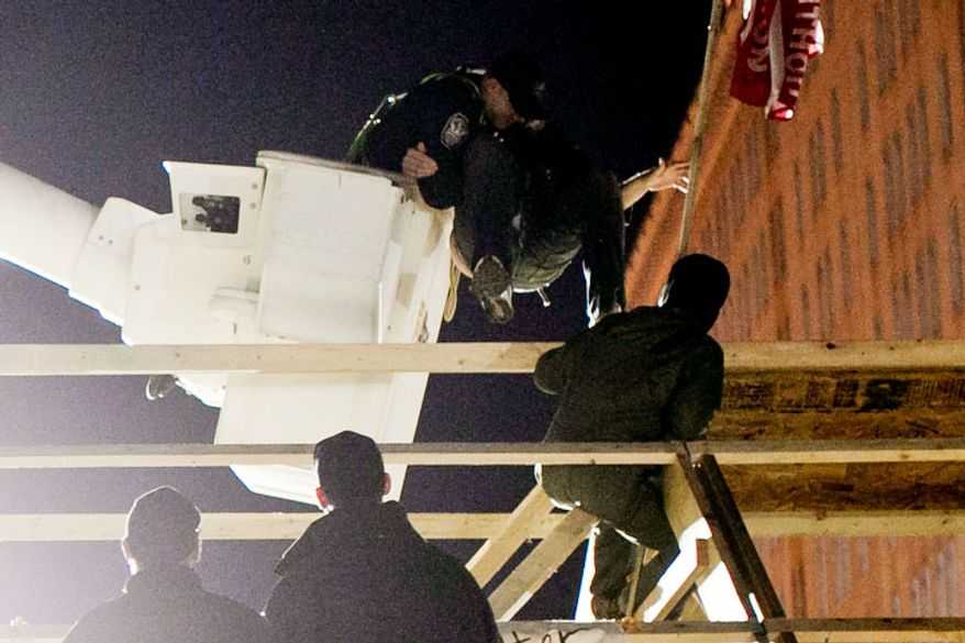Park Police use a cherry picker to pull a protestor off the roof of a new structure the was erected in McPherson Square, in Washington, D.C. on Dec. 4, 2011.