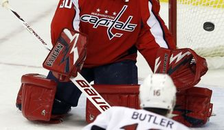 Washington Capitals goalie Michal Neuvirth deflects a shot by Ottawa Senators right wing Bobby Butler during the first period in Washington, Saturday, Dec. 3, 2011. (AP Photo/Ann Heisenfelt)