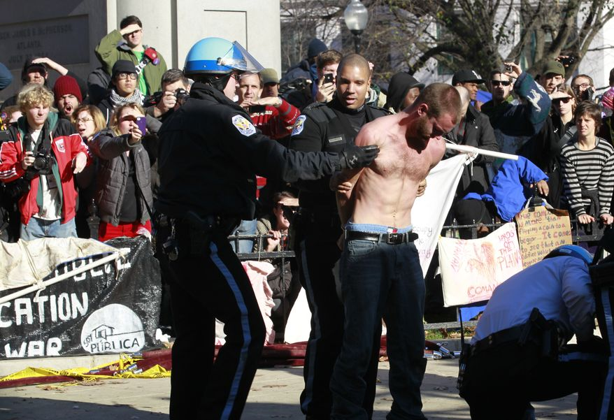An unidentified protestor is arrested in McPherson Square in downtown Washington Sunday, Dec. 4, 2011. U.S. Park Police are arresting Occupy DC protesters who are refusing to dismantle an unfinished wooden structure erected in the park square overnight. Police Sunday told the protestors they'd need a permit for such a structure and gave them an hour to disassemble it. (AP Photo/Manuel Balce Ceneta)
