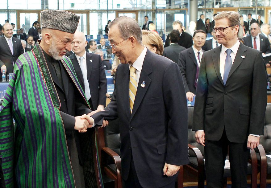Afghanistan President Hamid Karzai shakes hands with U.N. Secretary General Ban Ki-moon (center), while German Foreign Minister Guido Westerwelle (right) stands next to them at the International Afghanistan Conference in Bonn on Monday. (Associated Press)