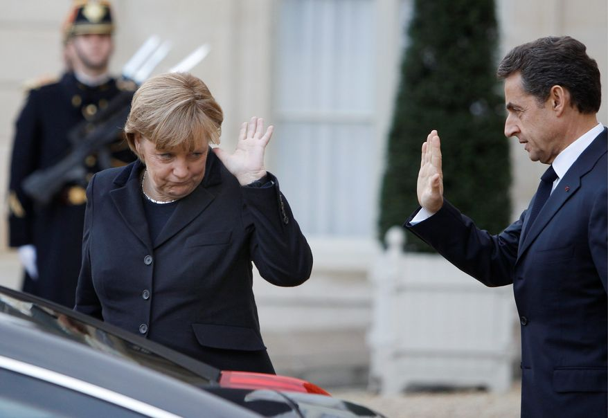 French President Nicolas Sarkozy waves goodbye to German Chancellor Angela Merkel on Monday as she leaves the Elysee Palace after their meeting in Paris. The two leaders discussed a cohesive plan to help save the euro through stricter oversight of government budgets. The warning by Standard & Poor's of a possible credit downgrade of European nations over the debt crisis came after U.S. financial markets closed Monday. (Associated Press)