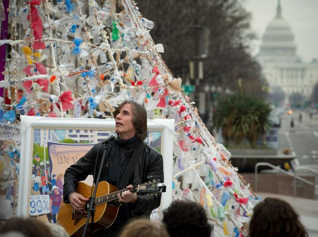 With the U.S. Capitol in the distance, singer Jackson Browne performs for a small crowd at Freedom Plaza, the site of a protest encampment, on Monday. (Rod Lamkey Jr/ The Washington Times)