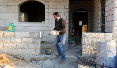 Palestinian Muayad Abdel Samed, 50, works at the construction site of his house in the West Bank village of Anabta. Mr. Samed, who spent half his life behind bars for killing an Israeli border police officer, is building his house with an $8,000 government grant. (Associated Press)