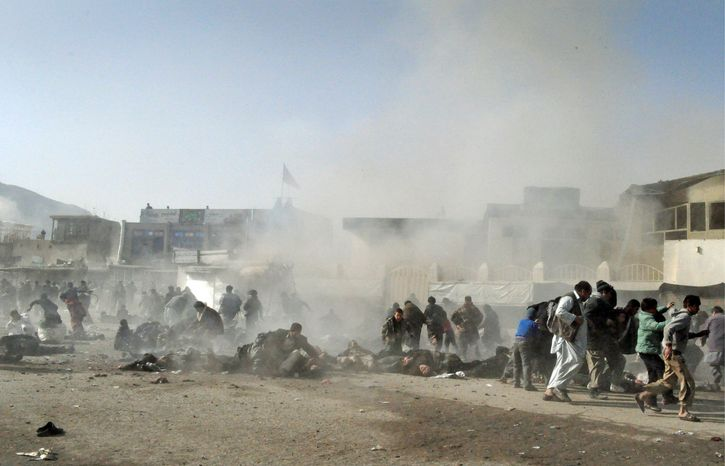 """Smoke and dust rises at the scene of a suicide bomb attack Tuesday that killed 56 during a Muharram procession outside the Abul Fazl shrine in Kabul, Afghanistan. """"It was a very powerful blast. ... Everyone was crying, shouting,"""" said Mahood Khan, who is in charge of the shrine near the presidential palace. """"It is a disaster."""" (Associated Press)"""