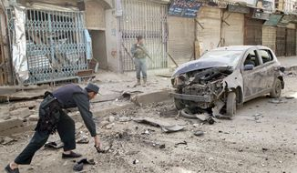 Afghan policemen pick up debris after a motorcycle bomb Tuesday in Kandahar killed a civilian. Unlike other explosions Tuesday, police said this one did not target Shiites. (Associated Press)