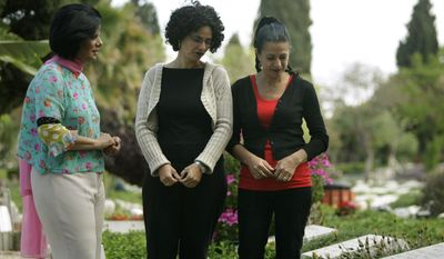 Dalia Goldman (left), Rachel Alon-Margalit (center) and Yael Alon-Rosenschein visit their father's grave in Tel Aviv. The slaying of Israeli Col. Joseph Alon remains a mystery four decades later. (Associated Press)