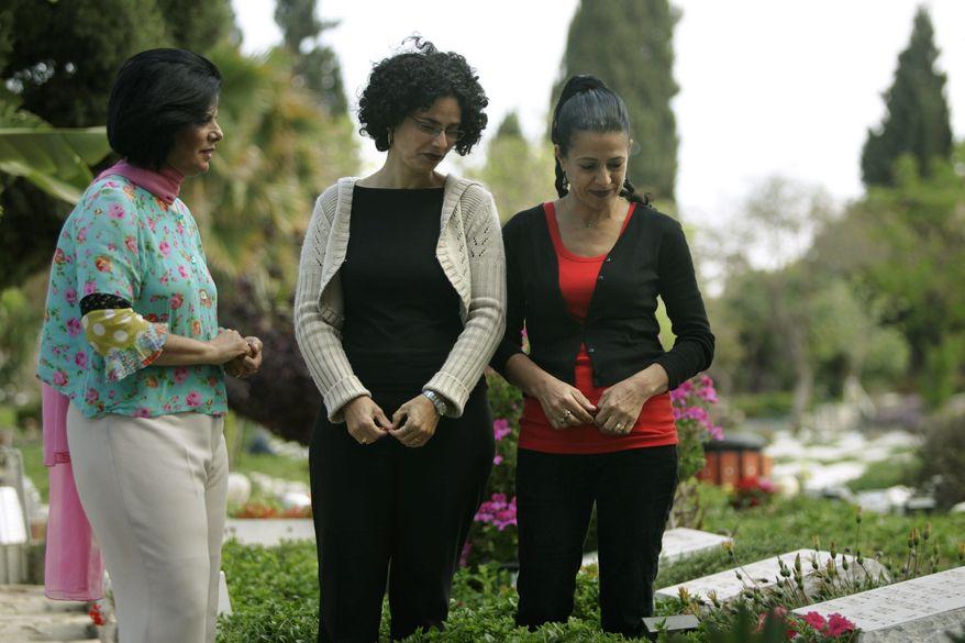 Dalia Goldman (left), Rachel Alon-Margalit (center) and Yael Alon-Rosenschein visit their father's grave in Tel Aviv. The slaying of Israeli Col. Joseph Alon remains a mystery four decades later. (Associated Press)