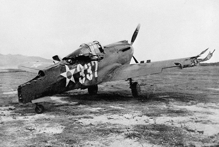 This is one of the first pictures of the Japanese raid on Pearl Harbor, Dec. 7, 1941. A P-40 plane which was machine-gunned while on the ground. (AP Photo)