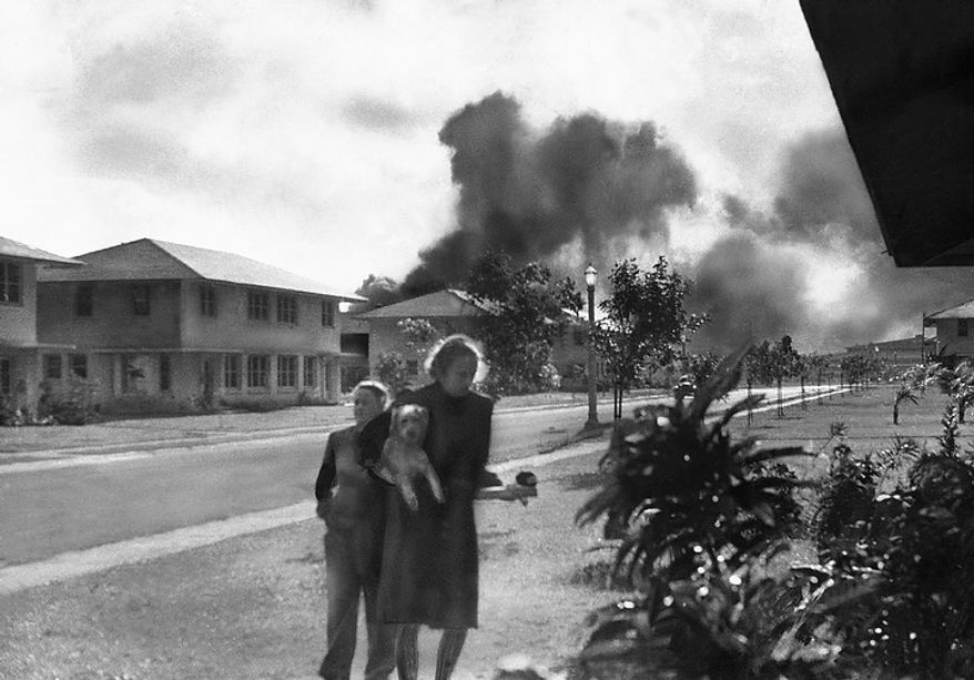 """Officers' wives, investigating explosion and seeing smoke pall in distance on Dec. 7, 1941, heard neighbor Mary Naiden, then an Army hostess who took this picture, exclaim """"There are red circles on those planes overhead. They are Japanese!"""" Realizing war had come, the two women, stunned, start toward quarters. (AP Photo/Mary Naiden)"""