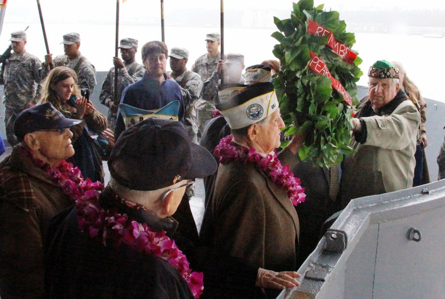 Pearl Harbor survivors (front row, from left) Robert Welkner, Aaron Chabin and John Jankowski prepare to cast a wreath into the Hudson River in New York aboard the Intrepid Sea, Air & Space Museum to commemorate the 70th anniversary of the Japanese attack on Pearl Harbor on Dec. 7, 1941. (Associated Press)