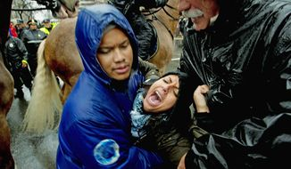 A woman is caught between people and a police horse as Metropolitan Police clear the street and make arrests during a protest in the intersection of 14th and K Streets NW in Washington, D.C., Wednesday, December 7, 2011. (Rod Lamkey Jr./The Washington Times)
