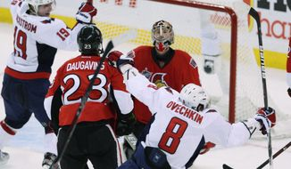 Washington Capitals' Alex Ovechkin celebrates his go-ahead goal along with teammate Nickolas Backstrom, who had a goal and an assist, during the third period in Ottawa, Ontario on Wednesday, Dec. 7, 2011. The Caps went on to win 5-3. (AP Photo/The Canadian Press, Fred Chartrand)